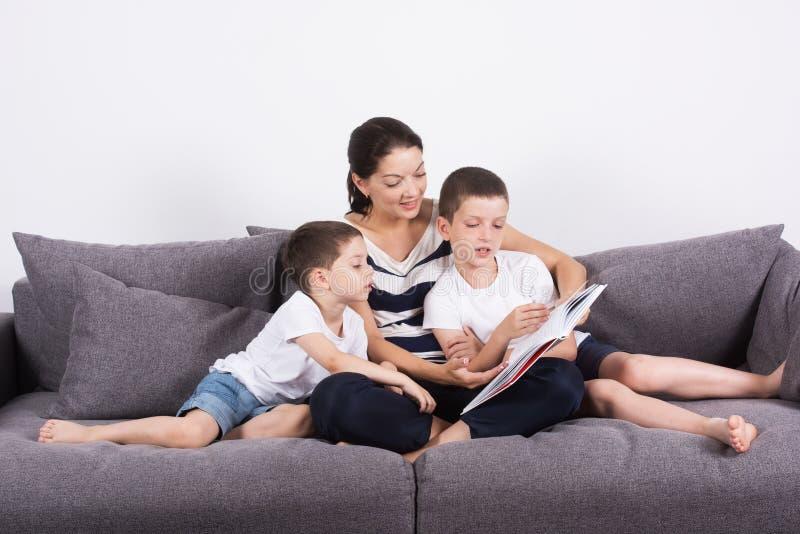 Η μητέρα διαβάζει ένα ενδιαφέρον βιβλίο με τους γιους της του καναπέ στοκ φωτογραφίες με δικαίωμα ελεύθερης χρήσης