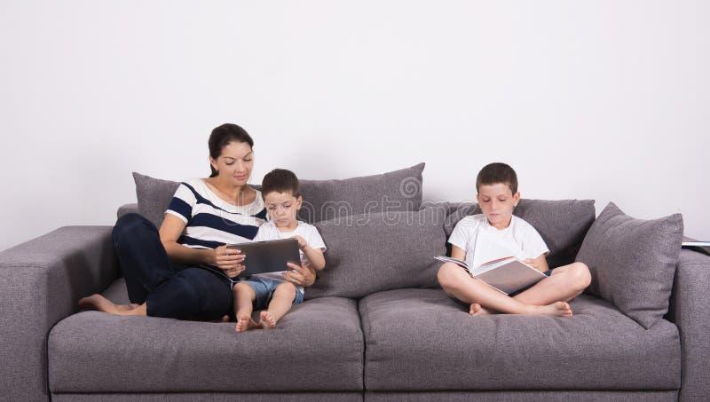 Η μητέρα διαβάζει ένα ενδιαφέρον βιβλίο με τους γιους της του καναπέ στοκ εικόνες