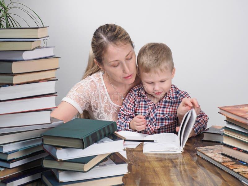 Η μητέρα διδάσκει το γιο για να διαβάσει μεταξύ των σωρών των βιβλίων στοκ εικόνα