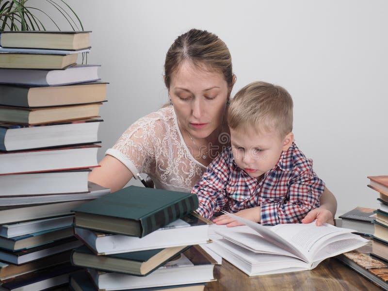 Η μητέρα διδάσκει το γιο για να διαβάσει μεταξύ των σωρών των βιβλίων στοκ φωτογραφία