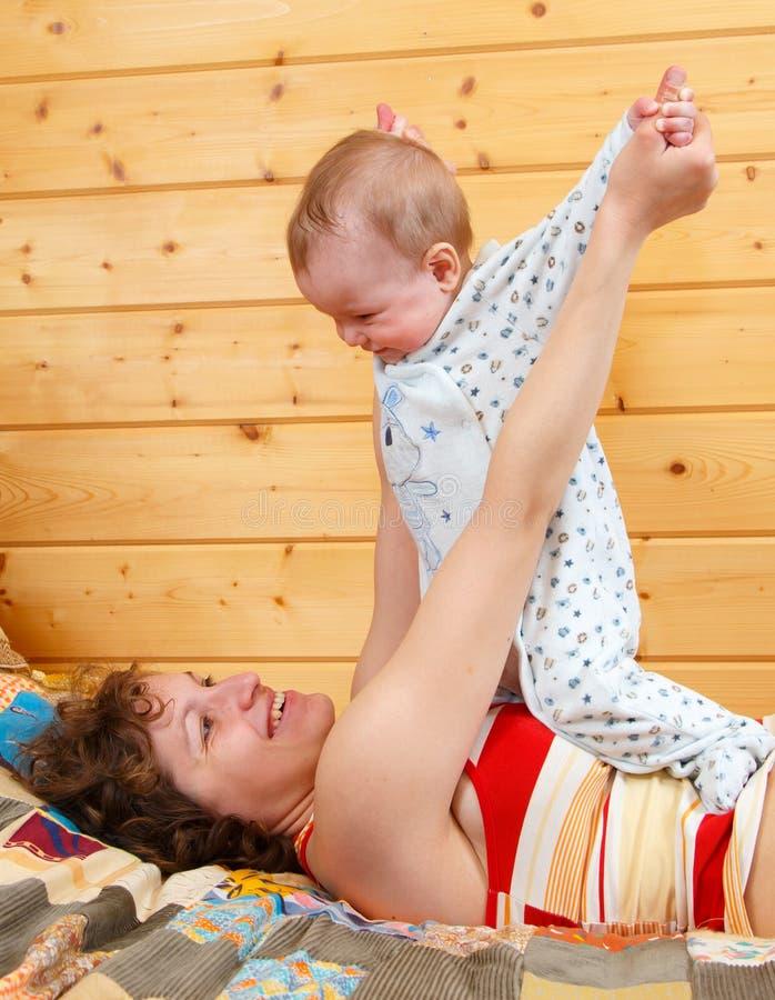 Η μητέρα κάνει τις ασκήσεις πρωινού με το μωρό της στοκ εικόνα