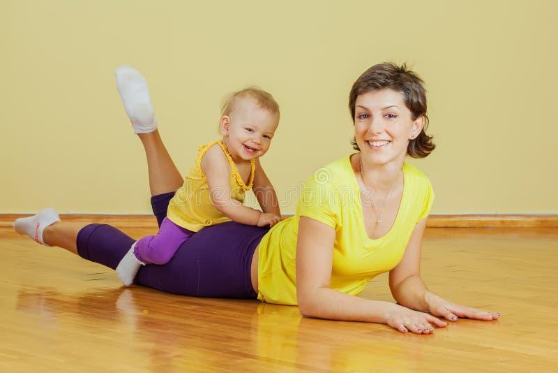 Η μητέρα κάνει τις σωματικές ασκήσεις με την κόρη της στοκ εικόνες