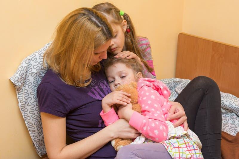 Η μητέρα και η παλαιότερη αδελφή μου ανακούφισαν το μικρό κορίτσι που αγκαλιάζει την σε τον και κτύπησαν στο κεφάλι στοκ εικόνα