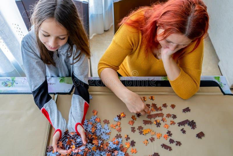 Η μητέρα και η κόρη κάνουν παζλ στο σαλόνι στο σπίτι στοκ εικόνες