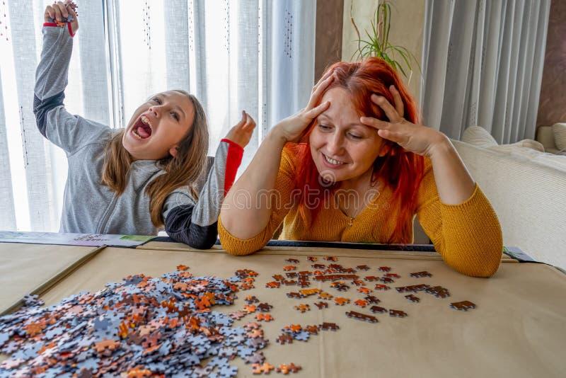 Η μητέρα και η κόρη κάνουν παζλ στο σαλόνι στο σπίτι στοκ εικόνα