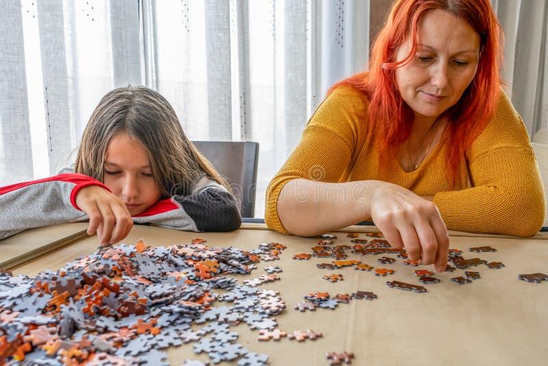 Η μητέρα και η κόρη κάνουν παζλ στο σαλόνι στο σπίτι στοκ φωτογραφίες