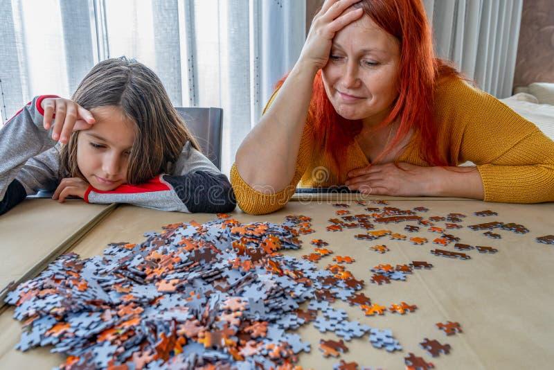Η μητέρα και η κόρη κάνουν παζλ στο σαλόνι στο σπίτι στοκ φωτογραφία