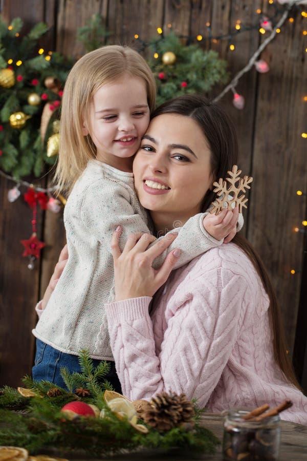 Η μητέρα και η κόρη κάνουν το στεφάνι Χριστουγέννων στοκ φωτογραφία