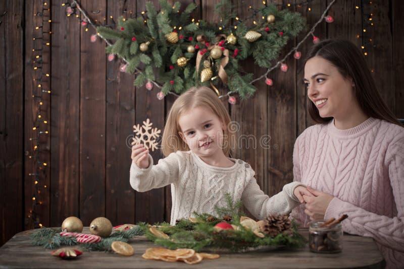 Η μητέρα και η κόρη κάνουν το στεφάνι Χριστουγέννων στοκ εικόνες