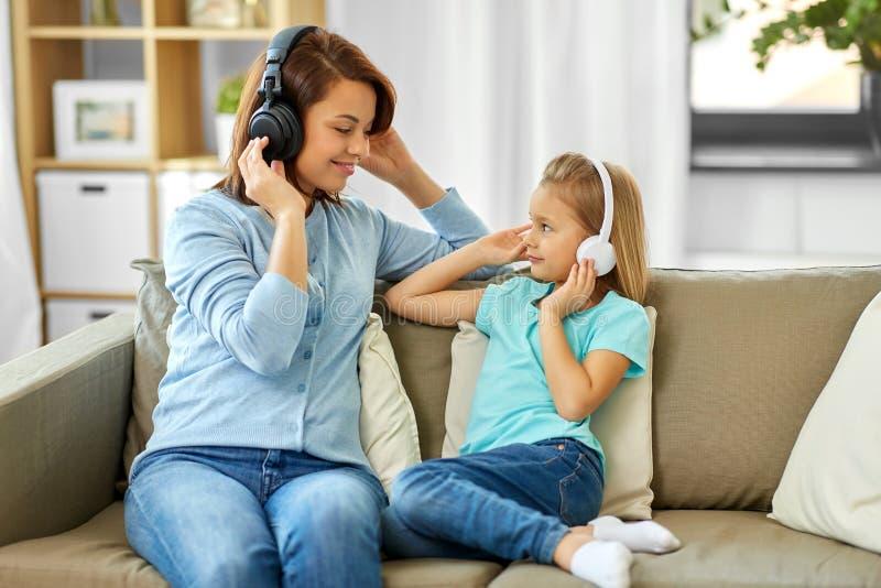 Η μητέρα και η κόρη στα ακουστικά ακούνε τη μουσική στοκ φωτογραφία με δικαίωμα ελεύθερης χρήσης