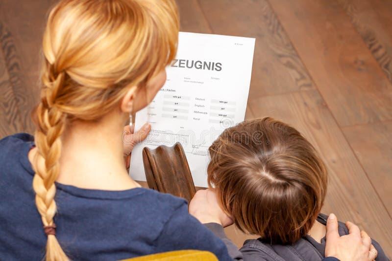 Η μητέρα και ο γιος είναι ευχαριστημένοι από το καλό σχολικό πιστοποιητικό - μετάφραση: ημέρα πιστοποιητικών της μουσικής πειθαρχ στοκ εικόνες