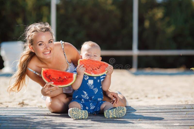 Η μητέρα και ο νέος γιος, τρώνε το ώριμο καρπούζι στοκ φωτογραφία με δικαίωμα ελεύθερης χρήσης