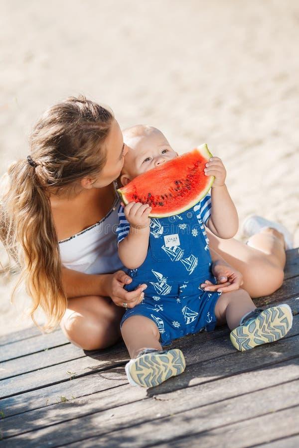 Η μητέρα και ο νέος γιος, τρώνε το ώριμο καρπούζι στοκ φωτογραφία