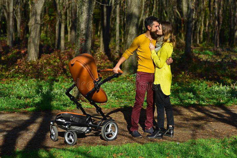 Η μητέρα και ο πατέρας με το καροτσάκι μωρών απολαμβάνουν την ημέρα άνοιξη Το ζεύγος ερωτευμένο με τον περιπατητή μωρών σταθμεύει στοκ εικόνες
