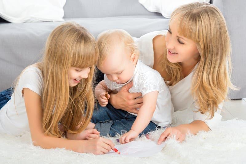 Η μητέρα και τα παιδιά σύρουν το μολύβι χρώματος στο σπίτι στοκ φωτογραφία με δικαίωμα ελεύθερης χρήσης