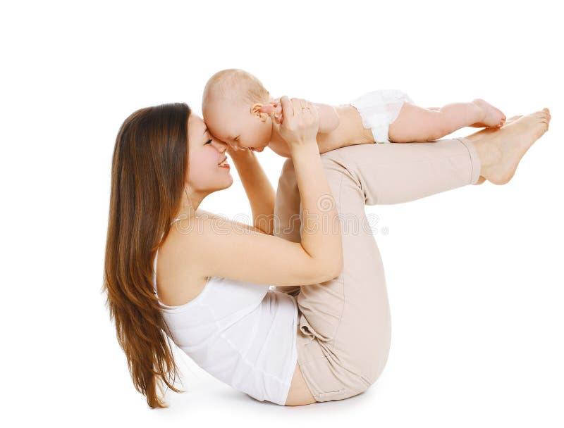 Η μητέρα και το μωρό κάνουν την άσκηση και έχουν τη διασκέδαση σε ένα whi στοκ εικόνες