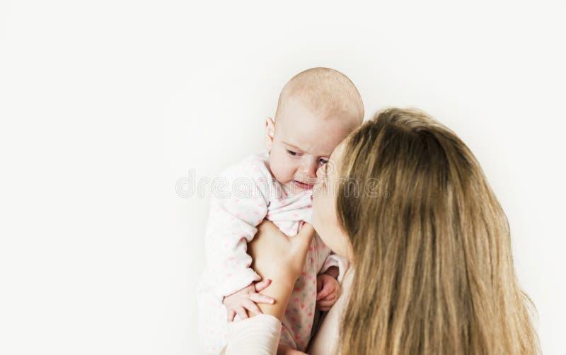Η μητέρα κρατά το μωρό στα όπλα της στο απομονωμένο υπόβαθρο στοκ εικόνες