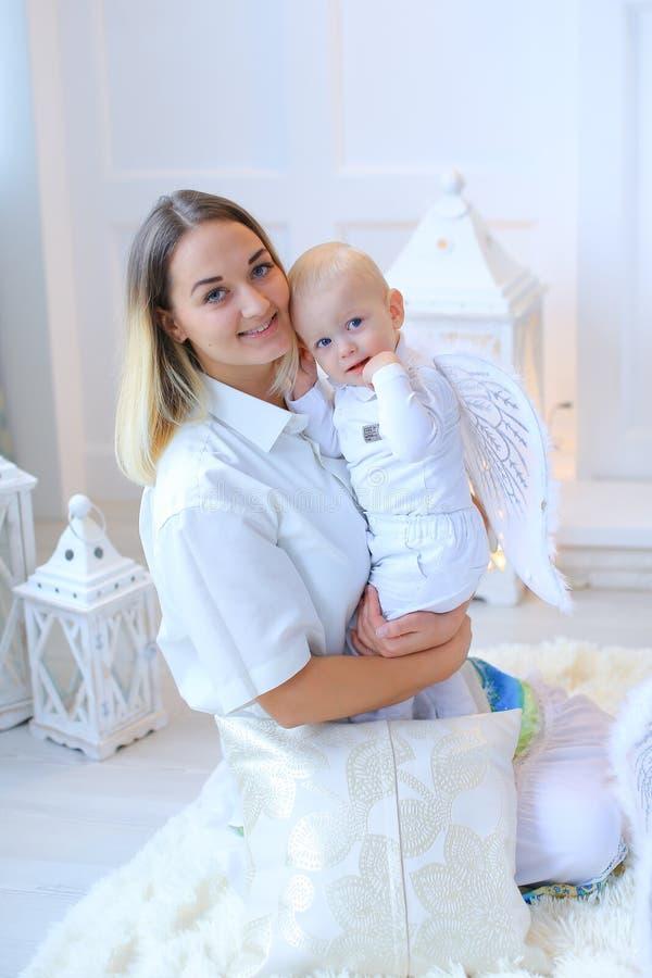 Η μητέρα με λίγο μωρό που χαμογελά, που θέτει και που γελά μέσα διακοσμεί στοκ φωτογραφίες