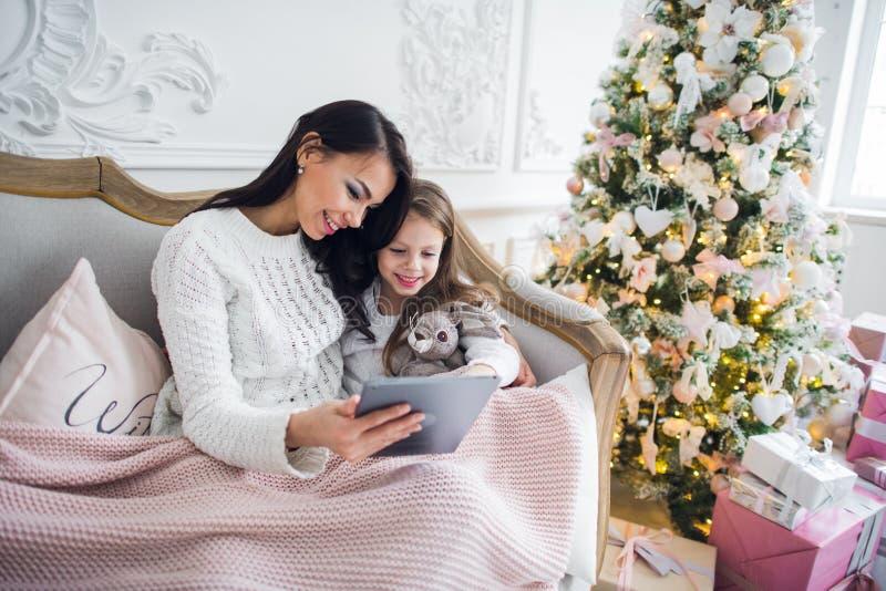 Η μητέρα με την κόρη στον καναπέ που χρησιμοποιεί την ευτυχή χαμογελώντας νέα οικογένεια υπολογιστών ταμπλετών διακόσμησε πλησίον στοκ εικόνα