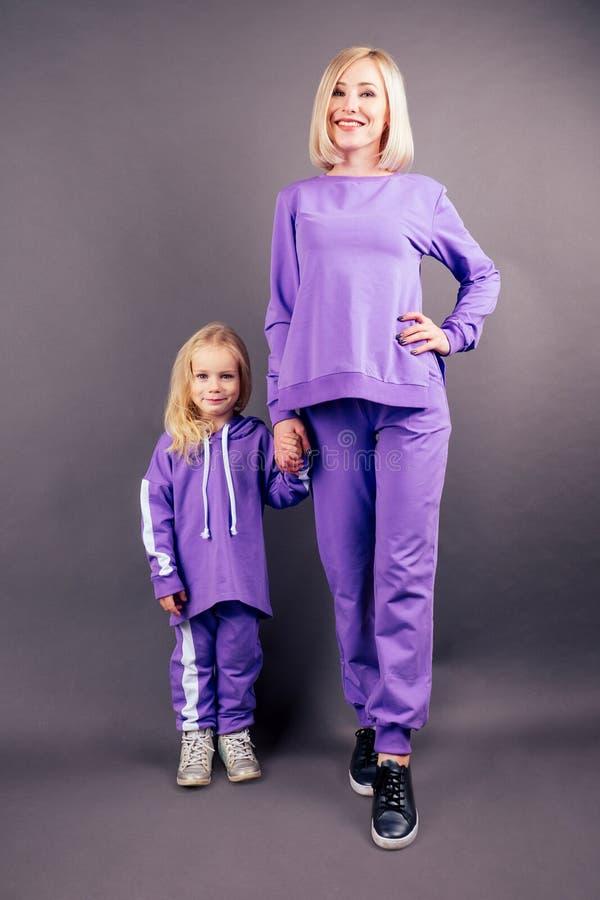Η μητέρα με την κόρη με τα ιώδη αθλητικά κοστούμια όμορφη και νεαρή ξανθιά γυναίκα με ένα μικρό κορίτσι να ποζάρει μοβ στοκ εικόνες