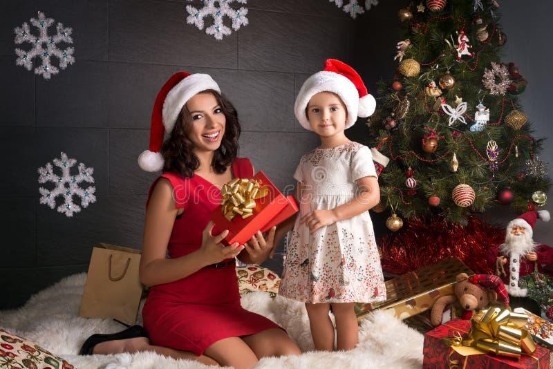 Η μητέρα με τις κόρες ανοίγει ένα δώρο Χριστουγέννων στοκ εικόνες