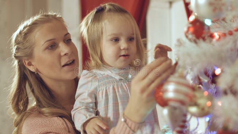 Η μητέρα με το λατρευτό μωρό διακοσμεί ένα χριστουγεννιάτικο δέντρο στο σπίτι στοκ εικόνα