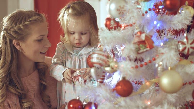 Η μητέρα με το λατρευτό μωρό διακοσμεί ένα χριστουγεννιάτικο δέντρο στο σπίτι στοκ φωτογραφία με δικαίωμα ελεύθερης χρήσης