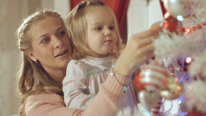 Η μητέρα με το λατρευτό μωρό διακοσμεί ένα χριστουγεννιάτικο δέντρο στο σπίτι στοκ φωτογραφία