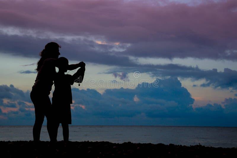 Η μητέρα με το γιο κάνει τις φωτογραφίες της θάλασσας στο ηλιοβασίλεμα με τα ρόδινα σύννεφα στοκ φωτογραφίες