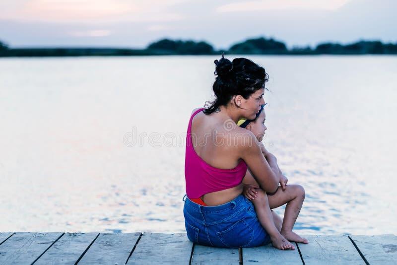Η μητέρα με το γιο της απολαμβάνει το όμορφο ηλιοβασίλεμα στοκ φωτογραφία με δικαίωμα ελεύθερης χρήσης