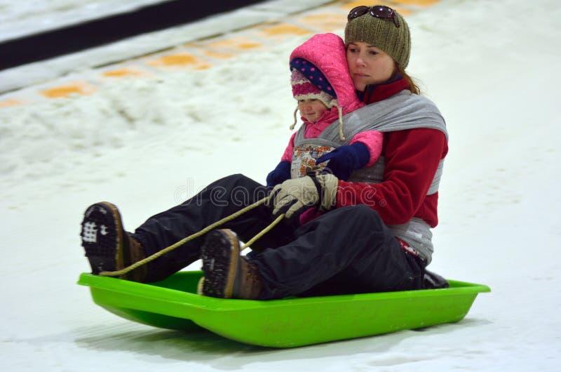 Η μητέρα με το παιδί σε ένα χιόνι γλίστρησε τη φωτογραφική διαφάνεια προς τα κάτω στοκ εικόνα