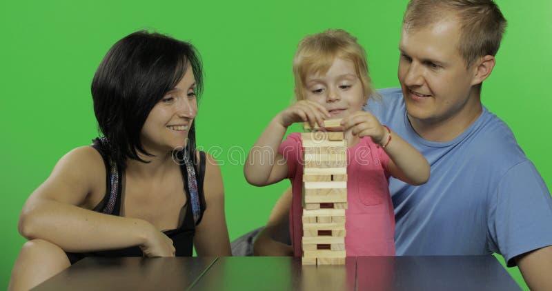 Η μητέρα, ο πατέρας και η κόρη παίζουν το jenga Τραβά τους ξύλινους φραγμούς από τον πύργο στοκ φωτογραφία με δικαίωμα ελεύθερης χρήσης