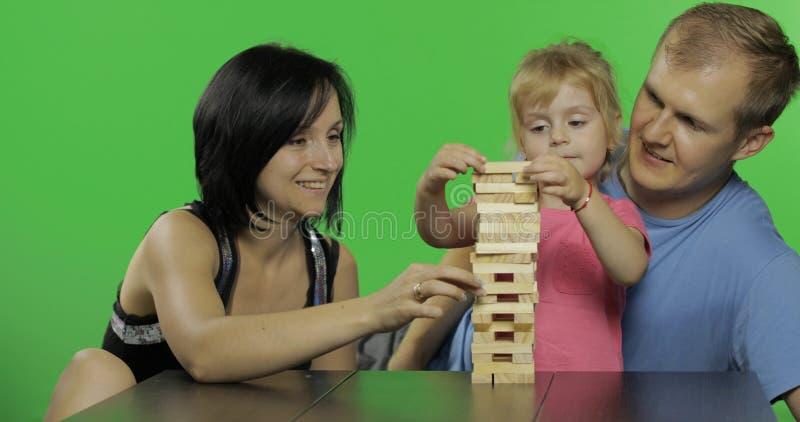 Η μητέρα, ο πατέρας και η κόρη παίζουν το jenga Τραβά τους ξύλινους φραγμούς από τον πύργο στοκ εικόνες