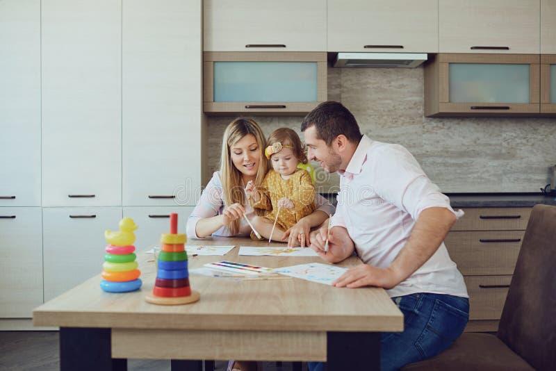 Η μητέρα, ο πατέρας και το παιδί σύρουν μαζί στον πίνακα στοκ εικόνα