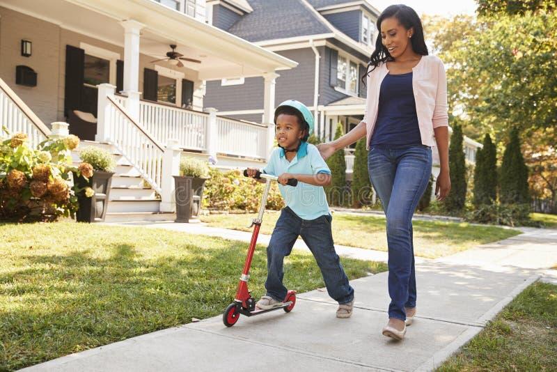 Η μητέρα περπατά με το γιο δεδομένου ότι οδηγά το μηχανικό δίκυκλο κατά μήκος του πεζοδρομίου στοκ εικόνα