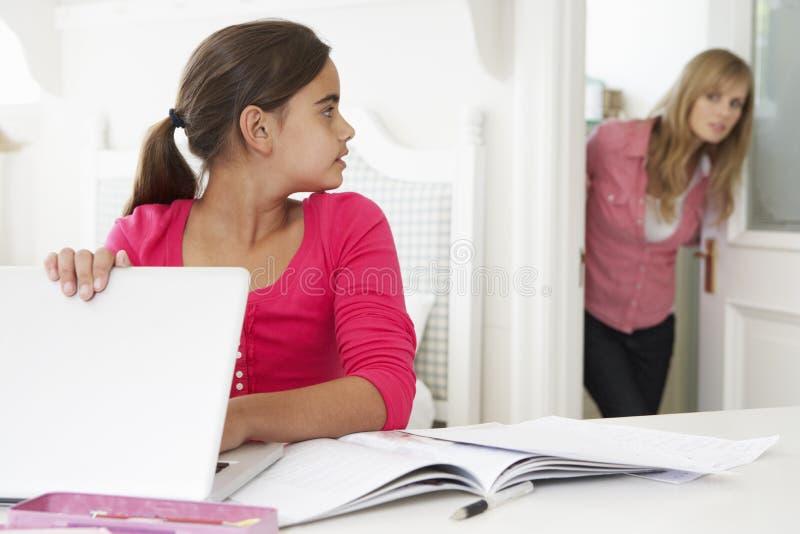 Η μητέρα πιάνει την κόρη χρησιμοποιώντας το lap-top όταν προορίζεται στοκ φωτογραφία