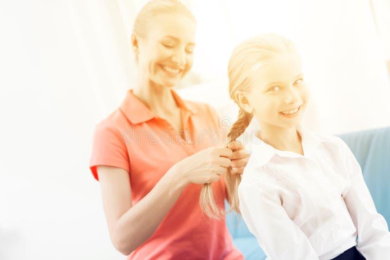 Η μητέρα πλέκει την τρίχα κορών της ` s Μια γυναίκα πλέκει μια πλεξούδα ένα μικρό κορίτσι στοκ φωτογραφίες