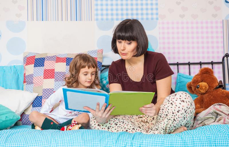 Η μητέρα της διαβάζει ένα ενδιαφέρον βιβλίο σε λίγη κόρη στοκ εικόνες