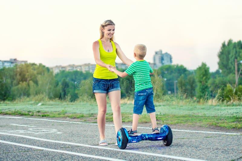 Η μητέρα της διδάσκει λίγο γιο για να οδηγήσει στον πίνακα ισορροπίας στοκ εικόνες