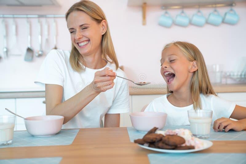 Η μητέρα τρέφει την όμορφη κόρη της με νιφάδες σοκολάτας και γελάει δυνατά διασκεδάστε μαζί, ντυμένοι στοκ φωτογραφία με δικαίωμα ελεύθερης χρήσης