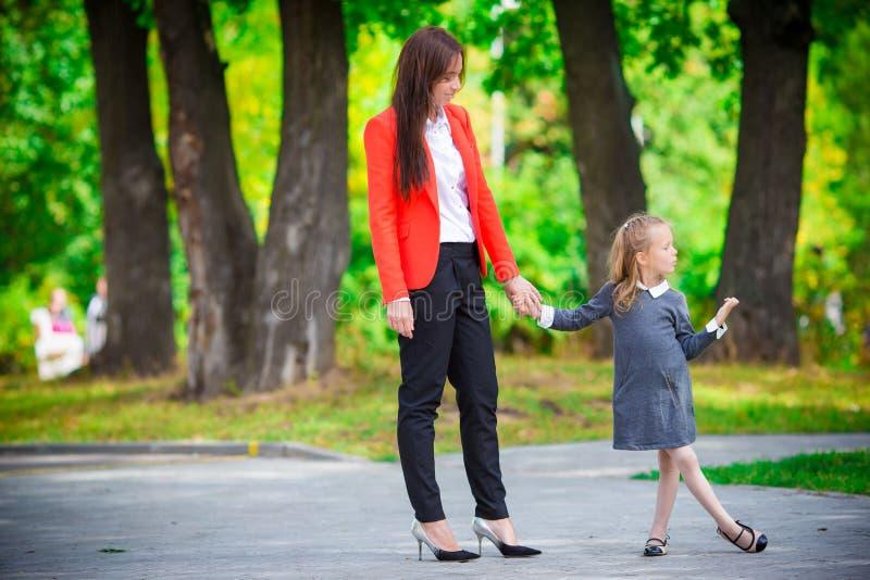 Η μητέρα φέρνει την κόρη της στο σχολείο Λατρευτό αίσθημα μικρών κοριτσιών πολύ που διεγείρεται για να πάει πίσω στο σχολείο στοκ φωτογραφία