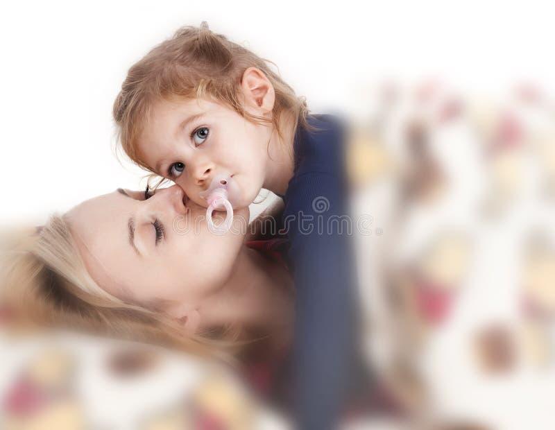 Η μητέρα φέρνει το παιδί της στο κρεβάτι στοκ εικόνα