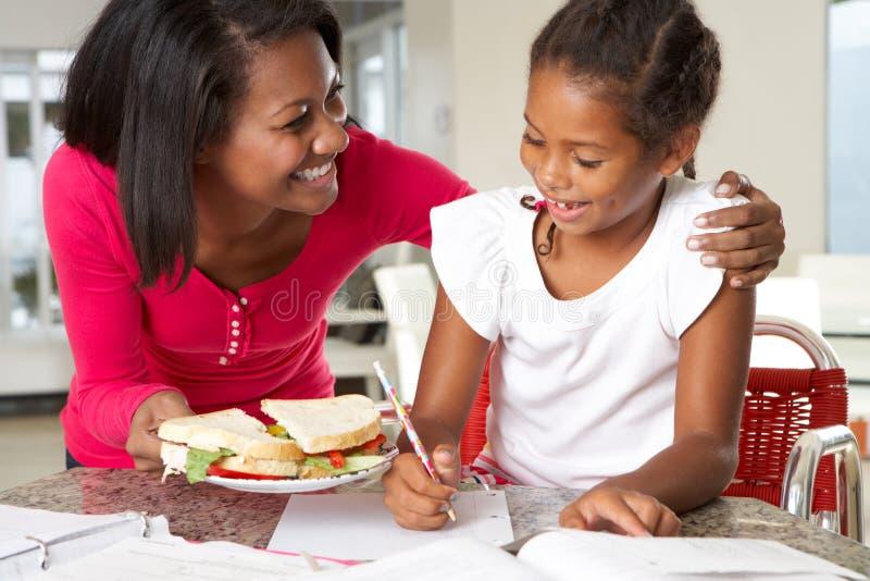 Η μητέρα φέρνει το σάντουιτς κορών ενώ μελετά στοκ εικόνες