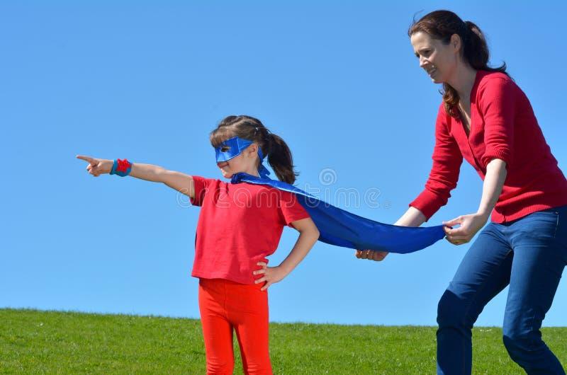 Η μητέρα Superhero παρουσιάζει κόρη της πώς να είναι ένα superhero στοκ εικόνα