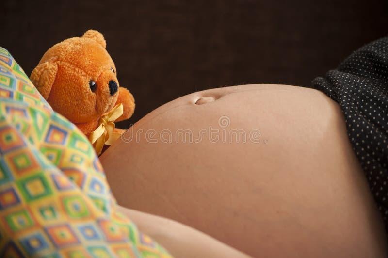 Η μητρότητα, έγκυος γυναίκα με χαριτωμένο πορτοκαλή teddy αντέχει στοκ φωτογραφία με δικαίωμα ελεύθερης χρήσης