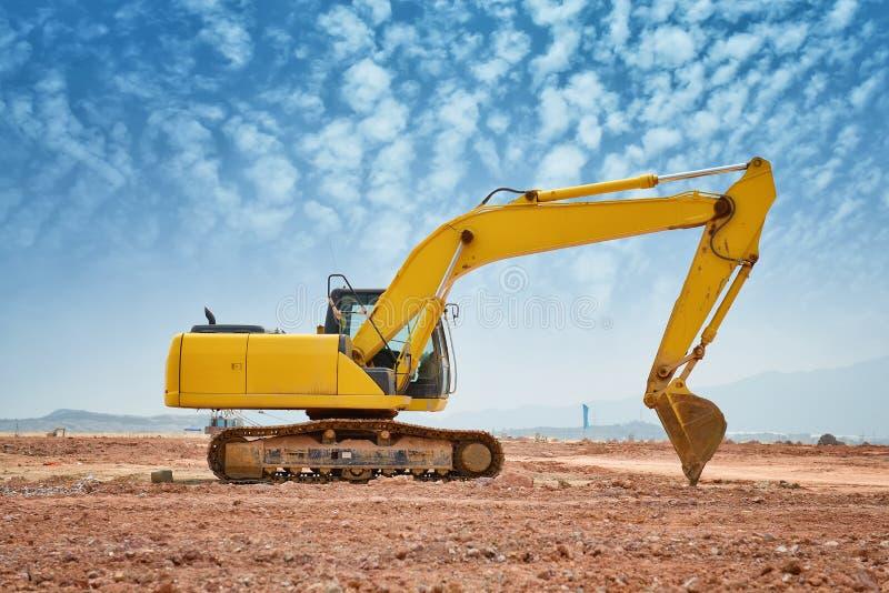 Η μηχανή φορτωτών εκσκαφέων κατά τη διάρκεια της κίνησης της γης λειτουργεί υπαίθρια στοκ φωτογραφίες