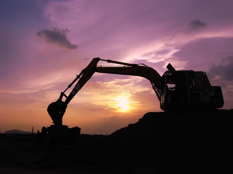 Η μηχανή φορτωτών εκσκαφέων κατά τη διάρκεια της κίνησης της γης λειτουργεί υπαίθρια στοκ φωτογραφία με δικαίωμα ελεύθερης χρήσης
