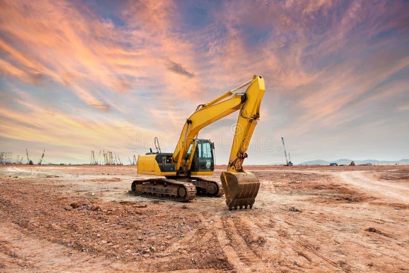 Η μηχανή φορτωτών εκσκαφέων κατά τη διάρκεια της κίνησης της γης λειτουργεί υπαίθρια στοκ εικόνες
