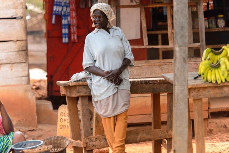 Η μη αναγνωρισμένη από τη Γκάνα ηλικιωμένη γυναίκα στο headscarf κλίνει στο woode στοκ φωτογραφίες με δικαίωμα ελεύθερης χρήσης