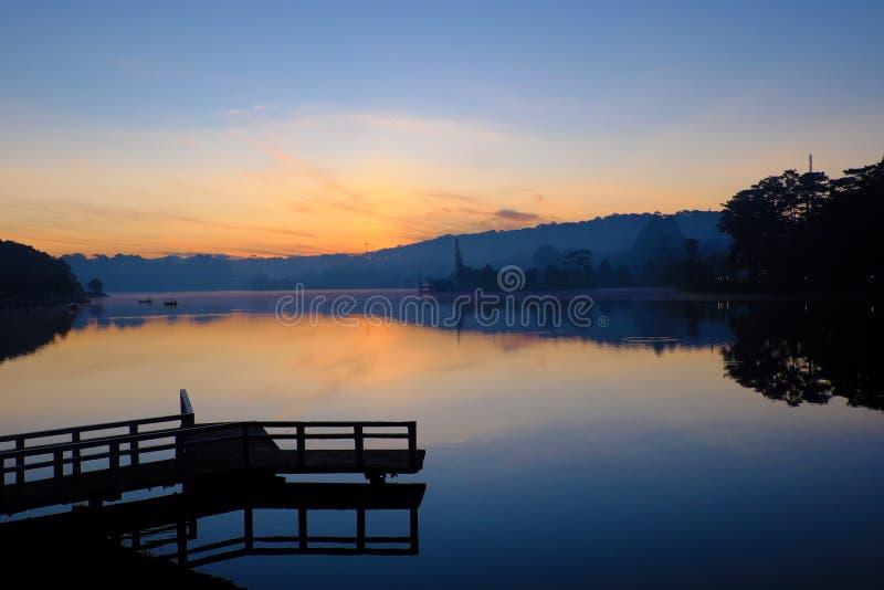Η μικρή γέφυρα απεικονίζει στη λίμνη στην ανατολή στοκ φωτογραφία